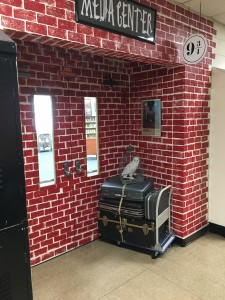 Photo of Gadsden Middle School Media Center Entrance which looks like a brick wall with luggage cart to resemble Platform 9 3/4 from the novel Harry Potter and the Sorcerer's Stone